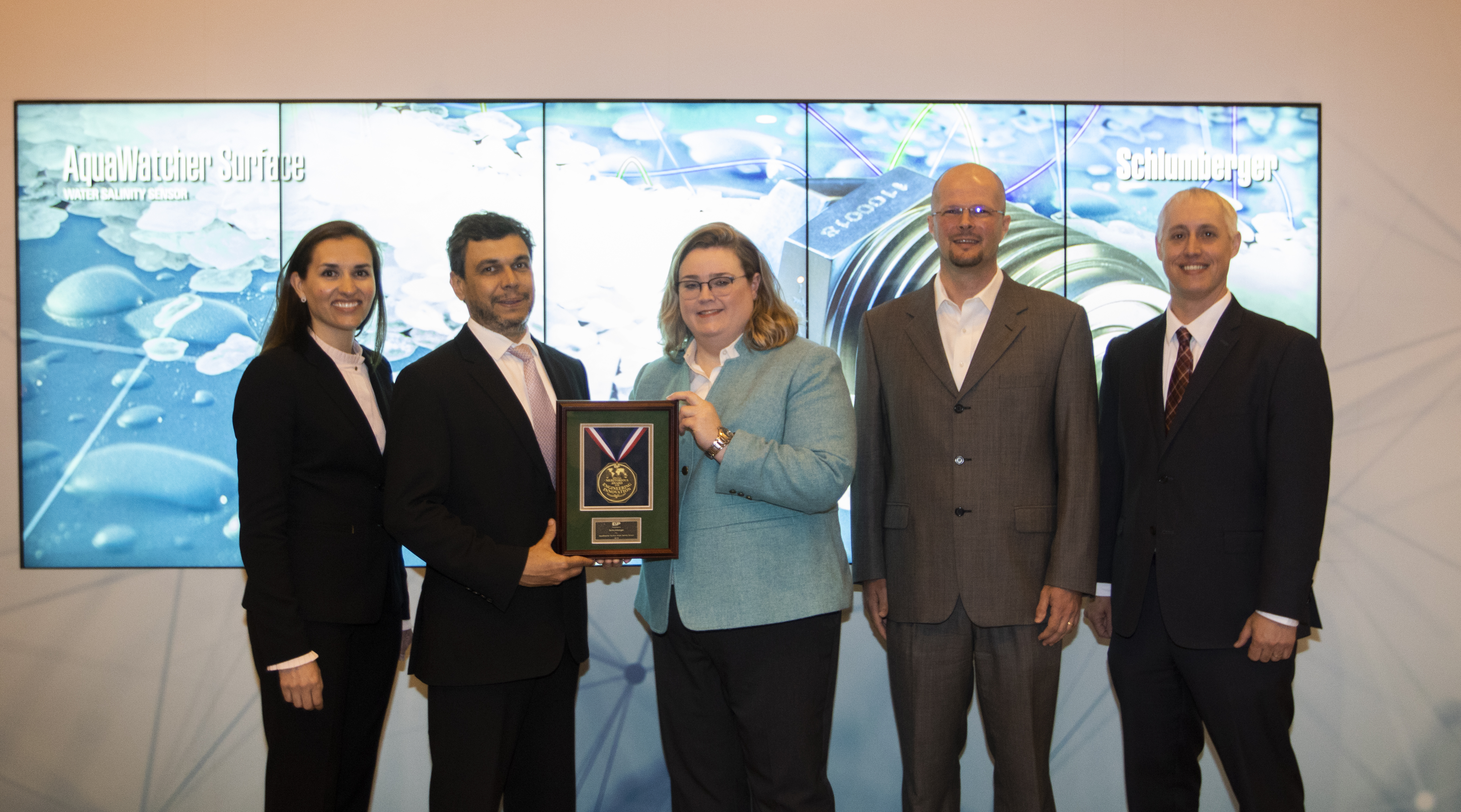 E&P's Jennifer Presley (middle) presented (from left to right) Schlumberger's Laure Mandrou, Wallace Pescarini, Baptiste Germond and Bryan Zimdars an award for the company's AquaWatcher Surface Water Salinity Sensor, winner of the water management category.
