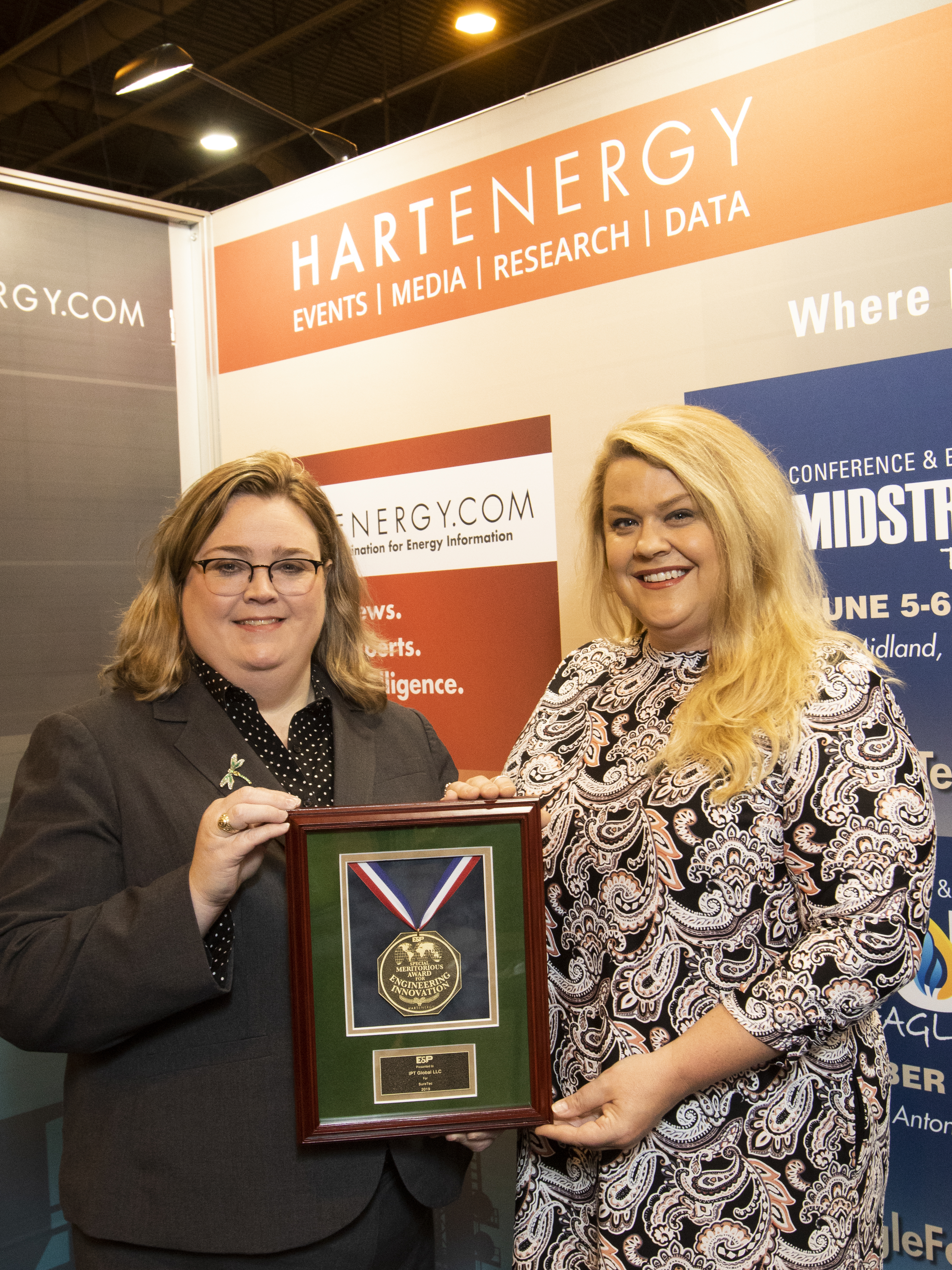 E&P's Jennifer Presley (left) presented an award to Kara French (right) of IPT Global LLC for SureTec, winner of the intelligent systems and components category.