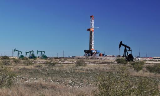 A drilling rig and pumpjacks are shown in a West Texas oil field. (Source: G.B. Hart/Shutterstock.com)