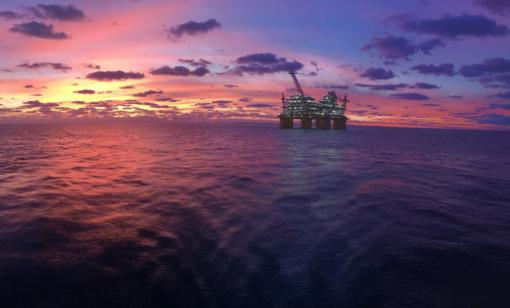 An oil production platform is shown at sunset in the Gulf of Mexico. (Source: revy252/Shutterstock.com)