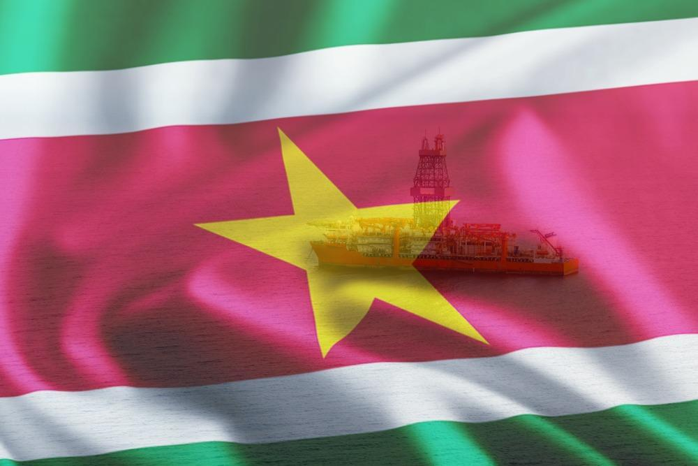 Pictured Suriname flag and drillship Noble Sam Croft, which was used to drill the Maka Central-1 offshore Suriname on Block 58. (Source: Noble Corp. Plc/Shutterstock.com)